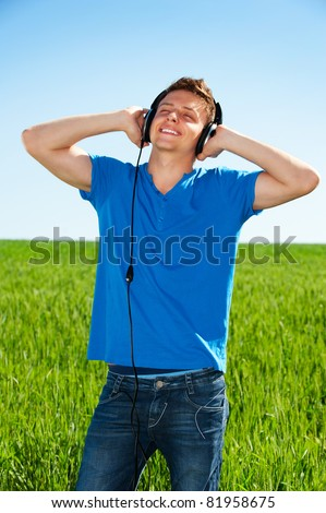 smiley man in headphones listening music with pleasure against blue sky and field - stock photo