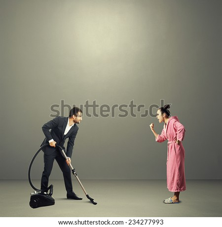 smiley man in suit holding vacuum cleaner and looking at screaming angry wife in pink dressing gown. photo in the grey room - stock photo