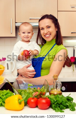 smiley mother and her son at the kitchen - stock photo