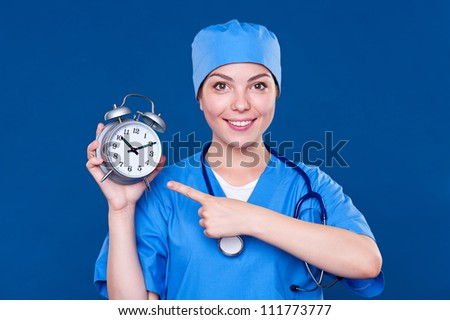 smiley nurse pointing at alarm clock. studio shot over blue background - stock photo