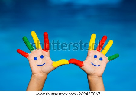 Smiley on hands against blue water background. Summer vacation concept - stock photo