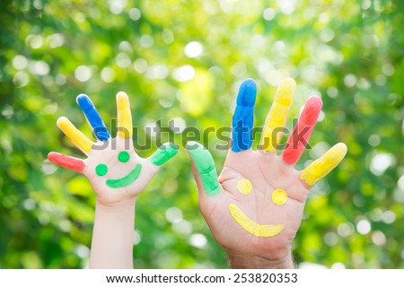 Smiley on hands against green spring background. Father and son having fun outdoors - stock photo
