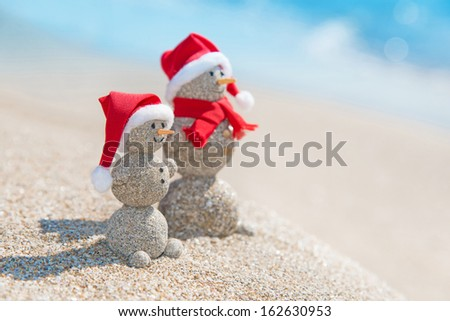 Smiley sandy snowmen couple at sea beach in christmas hat. New years holiday in hot countries concept. - stock photo