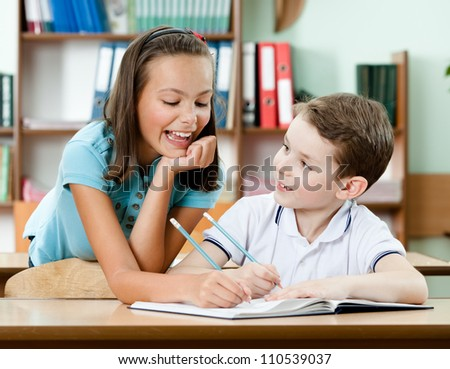 Smiley schoolgirl helps to her friend to do the task - stock photo