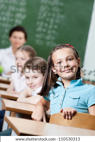 Smiley schoolgirl sits at the desk at math lesson - stock photo