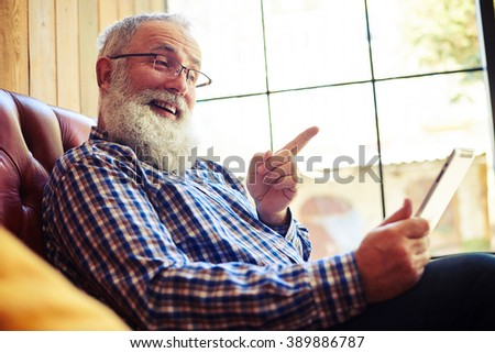 smiley senior man sitting on the couch  and pointing at tablet pc - stock photo