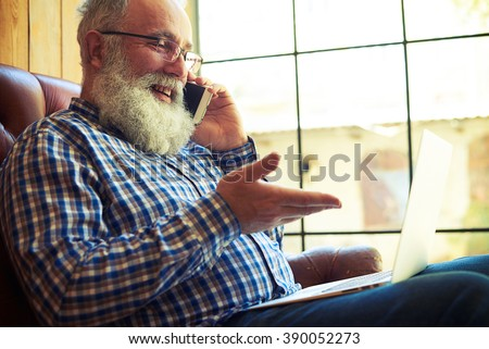 smiley senior man sitting on the couch with laptop and talking on the phone at home - stock photo