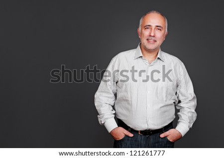 smiley senior man standing near empty copyspace. studio shot over grey background - stock photo