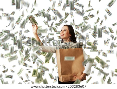 smiley successful businesswoman with paper bag catching money under dollar's rain - stock photo