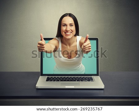 smiley woman stretching out of laptop and showing thumbs up against dark background - stock photo