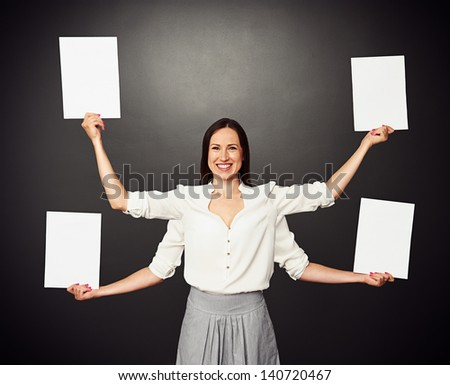 smiley woman with four hands holding white empty boards - stock photo