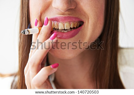 smiley woman with yellow dirty teeth holding cigarette - stock photo