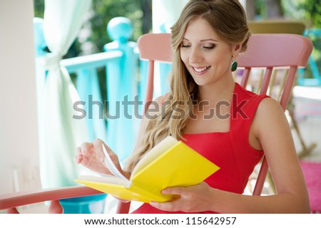 smiley young blonde reading the interesting book and smiling - stock photo