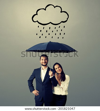 smiley young couple with black umbrella standing under drawing storm cloud. photo over grey background - stock photo