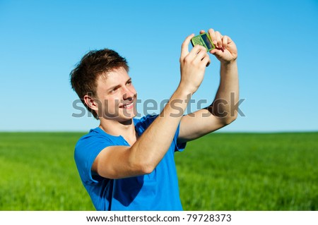 smiley young man taking picture on phone - stock photo