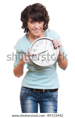 smiley young woman pointing at clock. isolated on white background - stock photo