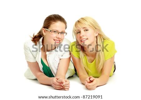 Smilimg girls lying on floor isolated - stock photo