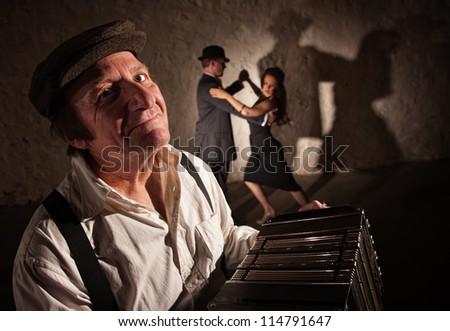 Smiling accordion player performing with dancers in the background - stock photo