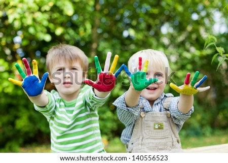 Smiling adorable children showing their colorful painted hands - stock photo