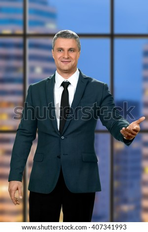 Smiling adult businessman's welcome gesture. Friendly official on skyscraper background. So happy to see you. Modesty and politeness. - stock photo