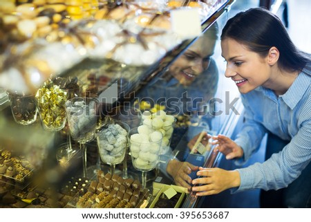 Smiling adult woman selecting fine chocolates and confectionery at cafe display - stock photo