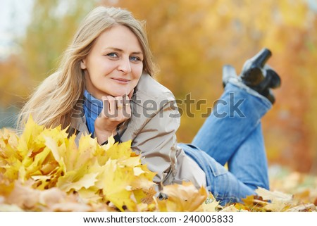 Smiling adult woman with autumn maple leaves wreath in park at fall outdoors - stock photo