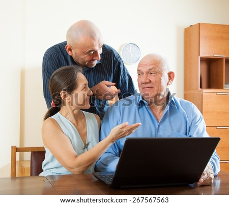 Smiling advisor  standing near mature couple with laptop - stock photo