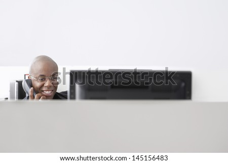 Smiling African American businessman using telephone at computer desk - stock photo