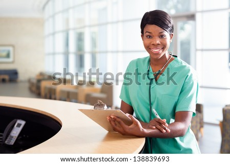 Smiling African American nurse at hospital work station lit brightly with clipboard and stethoscope. - stock photo