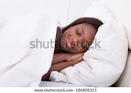Smiling African American woman sleeping in bed - stock photo
