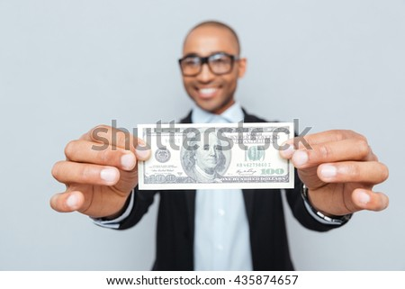 Smiling african american young man in glasses showing dollar banknote - stock photo