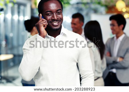 Smiling african businessman talking on the smartphone in front of colleagues - stock photo