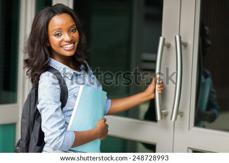 smiling african female college student going to lecture hall - stock photo