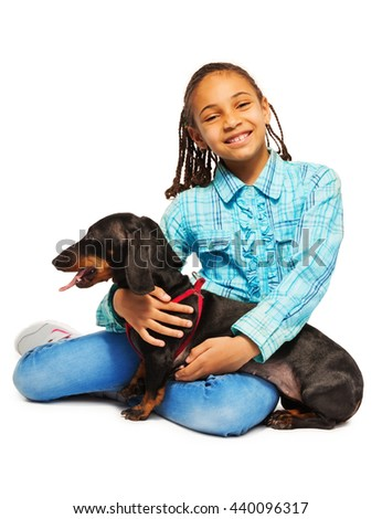 Smiling African girl hugging black dachshund  - stock photo