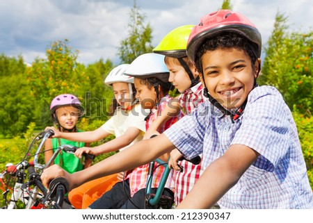 Smiling African guy in helmet with friends behind - stock photo