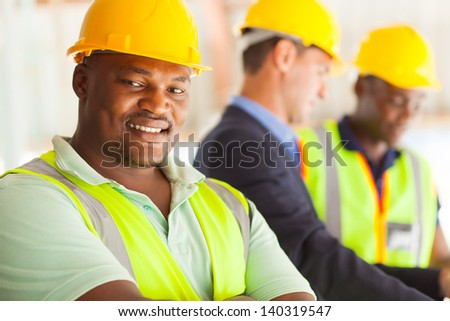 smiling african industrial engineer with colleagues - stock photo
