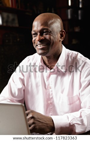 Smiling african man in pink shirt working at laptop and looking sideways - stock photo