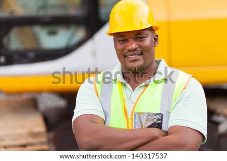 smiling african mine worker with arms folded at mining site - stock photo