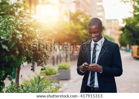 Smiling African professional using phone with city plants and sunflare - stock photo