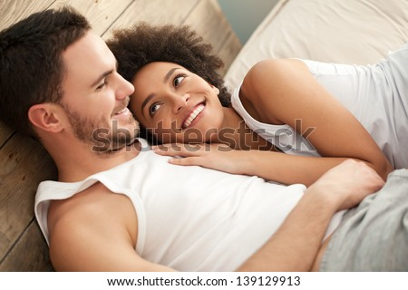 Smiling African woman lying in bed with her boyfriend. - stock photo