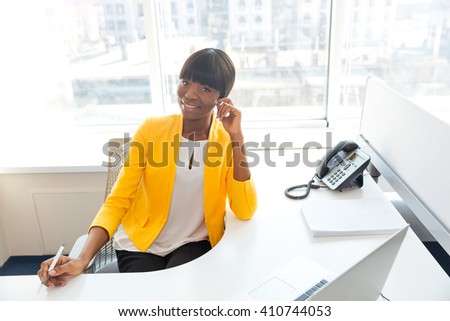 Smiling afro american businesswoman sitting at her workplace in office and looking at camera - stock photo