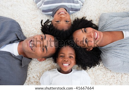 Smiling Afro-American family on floor with heads together - stock photo