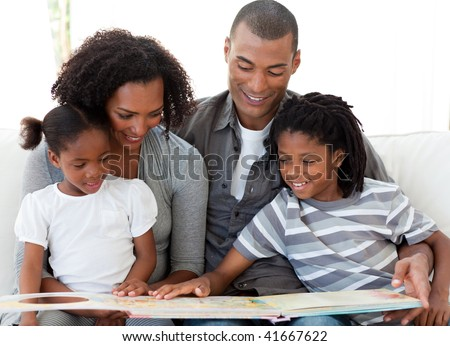 Smiling Afro-American family reading a book in the living-room - stock photo