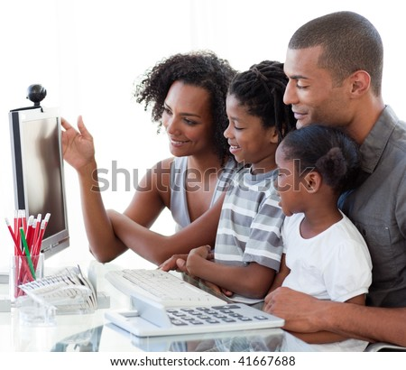 Smiling Afro-American family working with a computer at home - stock photo