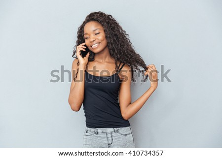 Smiling afro american woman talking on the phone over gray background - stock photo