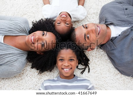 Smiling Afro-American young family lying on floor in a circle - stock photo