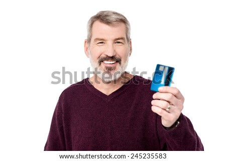 Smiling aged man holding up his debit card - stock photo