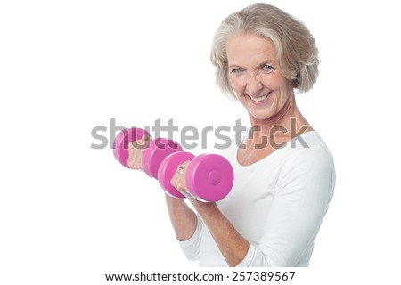 Smiling aged woman working out with dumbbells - stock photo