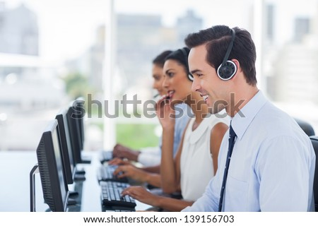 Smiling agent working in a call centre next to his colleagues - stock photo