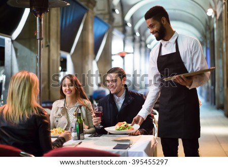 smiling american afro waiter taking table order and smiling in winter evening - stock photo